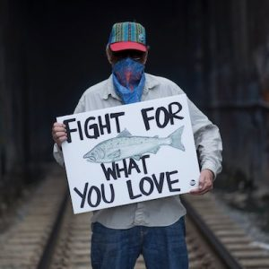 person holding sign reading fight for what you love